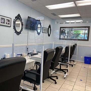 Plexiglass dividers between: spa pedicure chairs, manicure tables, nail drying stations and waiting area.